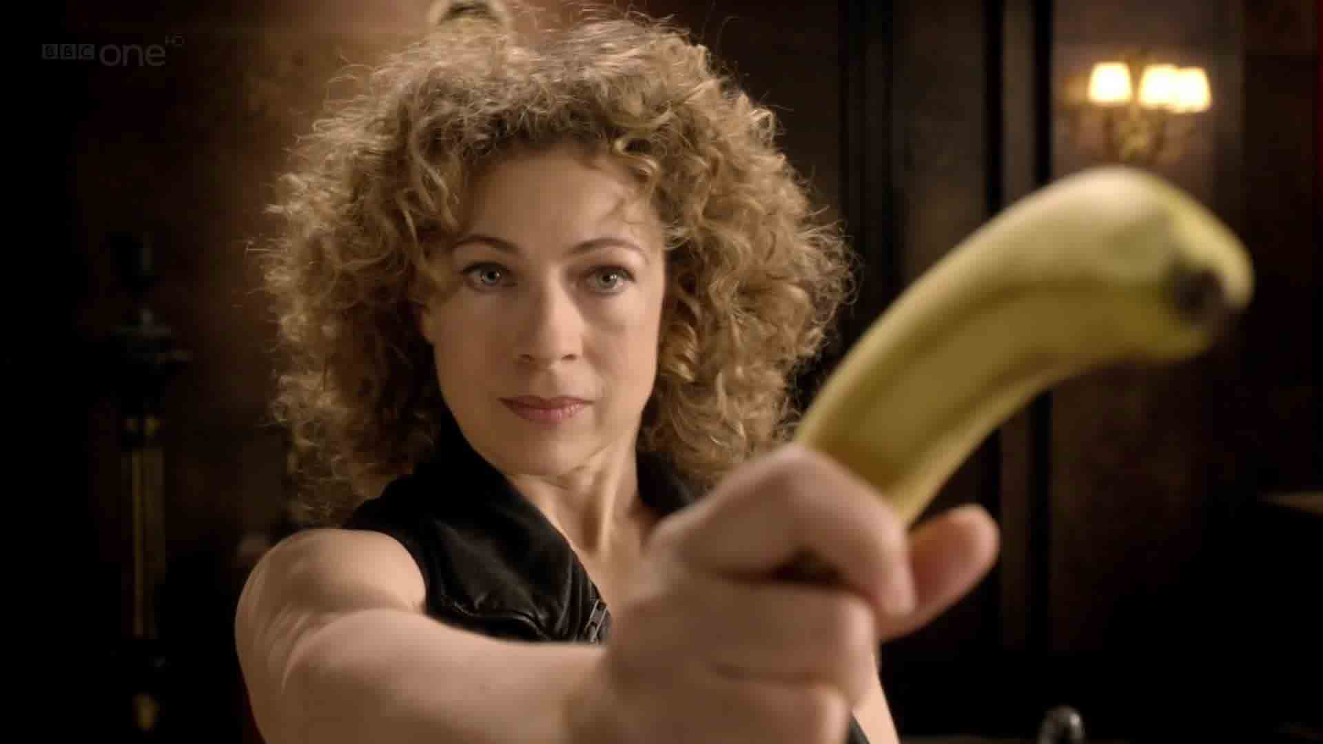 River Song holding a banana like a pistol