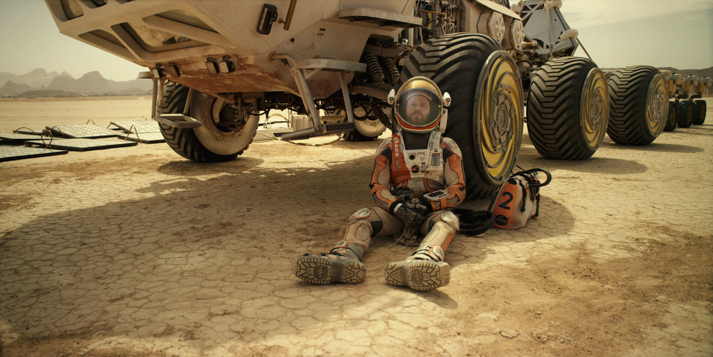 Matt Damon leaning on a Mars rover