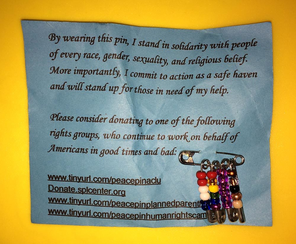 Safety pins with colorful beads on them, attached to a card encouraging donations